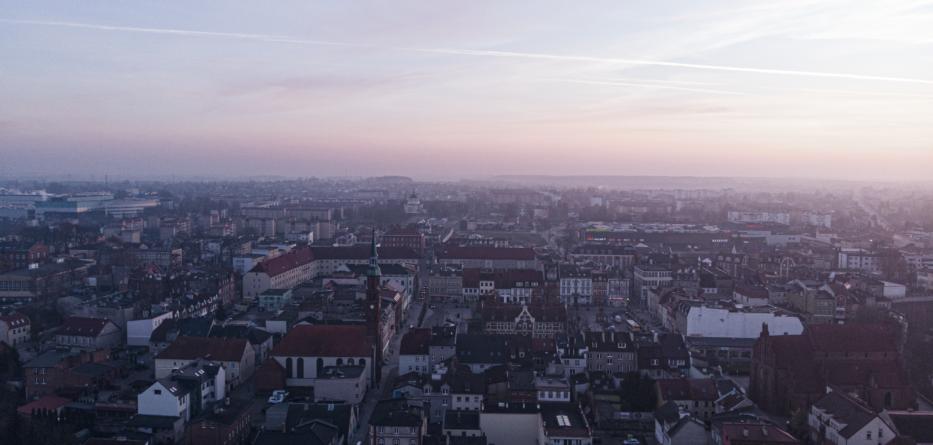 Widok z drona nad miastem Starogard Gdański - dużo domów i bloków na tle nieba